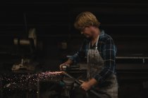 Blacksmith grinding a metal rod with grinder machine n workshop — Stock Photo
