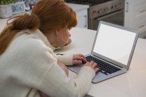 Donna rossa dei capelli utilizzando schermo monitor portatile in cucina a casa, bianco — Foto stock