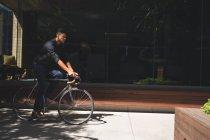 Молодой предприниматель, езда на велосипеде в офис — стоковое фото