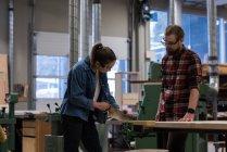 Tischlerin mit Handsäge, während der Mann sie in der Werkstatt ansieht — Stockfoto