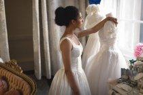 Жінка змішаної раси, наречена в Білій сукні, що дивиться крізь скло в бутік — стокове фото