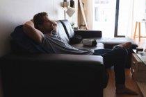 Détente sur le canapé dans le salon à la maison de l'homme — Photo de stock