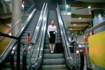 Donna in piedi sulla scala mobile con i bagagli all'aeroporto — Foto stock