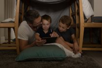 Father with his sons using digital tablet at home — Stock Photo