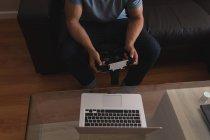 Uomo in possesso di auricolare realtà virtuale in soggiorno a casa — Foto stock