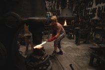 Кузнец формирует горячий металлический стержень в машине в мастерской — стоковое фото