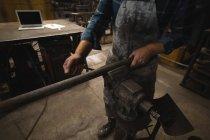 Ferreiro apertando haste de metal na oficina — Fotografia de Stock