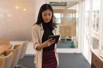 Young female executive using digital tablet in office — Stock Photo