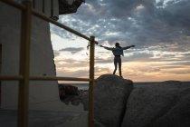 Vue arrière de la femme debout avec les bras tendus à la plage — Photo de stock