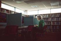 Jeune femme travaillant sur ordinateur dans la bibliothèque — Photo de stock