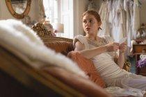 Молодий нареченою весільну сукню, проведення Примітка сидячи на дивані — стокове фото
