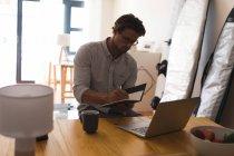 Hombre escribiendo en un diario mientras usa el portátil en casa - foto de stock
