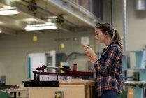 Женщина-плотник осматривает деревянную мебель в мастерской — стоковое фото