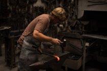 Вироби ковальські куванням розпеченого металу стрижня в майстерні — стокове фото