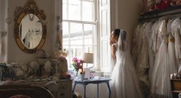 Mixed-race woman, bride in white dress looking through the window at vintage boutique — Stock Photo