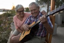 Happy senior couple playing guitar in the porch — Stock Photo