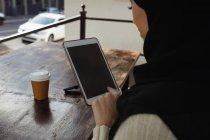 Primer plano de la mujer hijab usando tableta digital en la cafetería - foto de stock