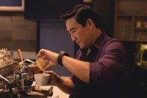 Male waiter preparing coffee in coffee shop — Stock Photo