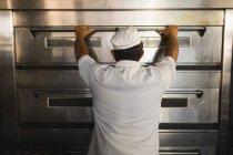 Visão traseira do padeiro masculino usando o forno owen na loja de padaria — Fotografia de Stock