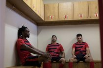 Football players relaxing on bench in dressing room — Stock Photo