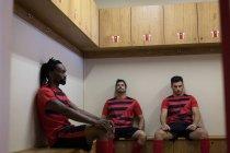 Fußballer, die entspannend auf Bank in Umkleidekabine — Stockfoto