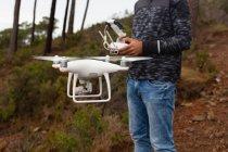 Человек, управляющий летающим дроном — стоковое фото
