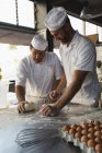 Male baker preparing dough with his coworker — Stock Photo