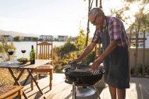 Старший чоловік приготування риби на барбекю у дворі — стокове фото