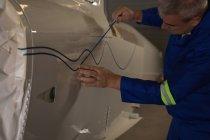 Mechanic marking a line on airplane parts at aerospace hangar — Stock Photo