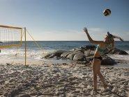 Weibliche Volleyball-Spieler Fußball spielen am Strand — Stockfoto