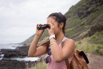 Young woman looking through binoculars in countryside — Stock Photo