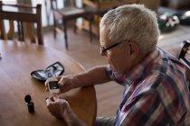 Uomo anziano che controlla lo zucchero nel sangue con glucometro a casa — Foto stock