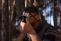 Close-up of man clicking photo with vintage camera in forest — Stock Photo