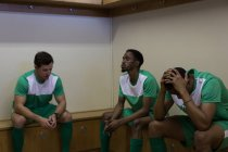Tense football players sitting on dressing room — Stock Photo