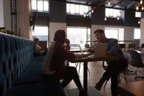 Collègues de travail interagissent entre eux dans la cafétéria du Bureau — Photo de stock