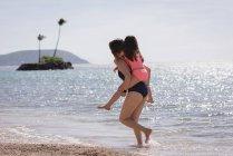 Madre con su hija un piggyback en la playa en un día soleado - foto de stock
