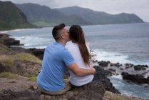 Вид сзади пара, обнимая друг друга возле моря — стоковое фото