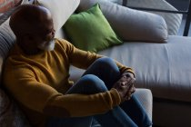 Thoughtful senior man relaxing on sofa at home — Stock Photo