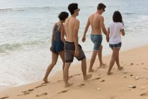 Two couples walking together hand in hand at beach — Stock Photo