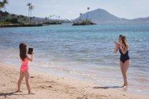 Filha de clicar a foto da mãe com tablet digital na praia — Fotografia de Stock