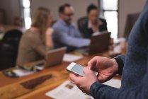 Mitte der männlichen Führungsriege mit Handy im Büro — Stockfoto