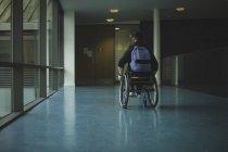 Homme handicapé en fauteuil roulant se déplaçant dans le passage à la salle de gym — Photo de stock