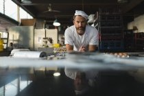 Portrait of male baker standing in bakery shop — Stock Photo