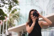 Женщина щелкает фото цифровой камерой в городе — стоковое фото