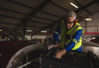 Engineer checking aircraft engine in hangar — Stock Photo