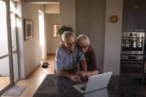 Senior couple video calling on laptop in kitchen at home — Stock Photo