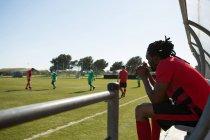 Vista lateral del jugador viendo el partido de fútbol desde dugout - foto de stock