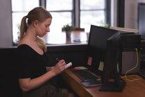 Weibliche Führungskraft auf Merkzettel am Schreibtisch im Büro schreiben — Stockfoto