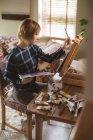 Женщина-художник рисует картину на холсте в гостиной на дому — стоковое фото