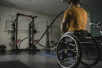 Handicappato su sedia a rotelle che si esercita con battaglia corde in palestra — Foto stock